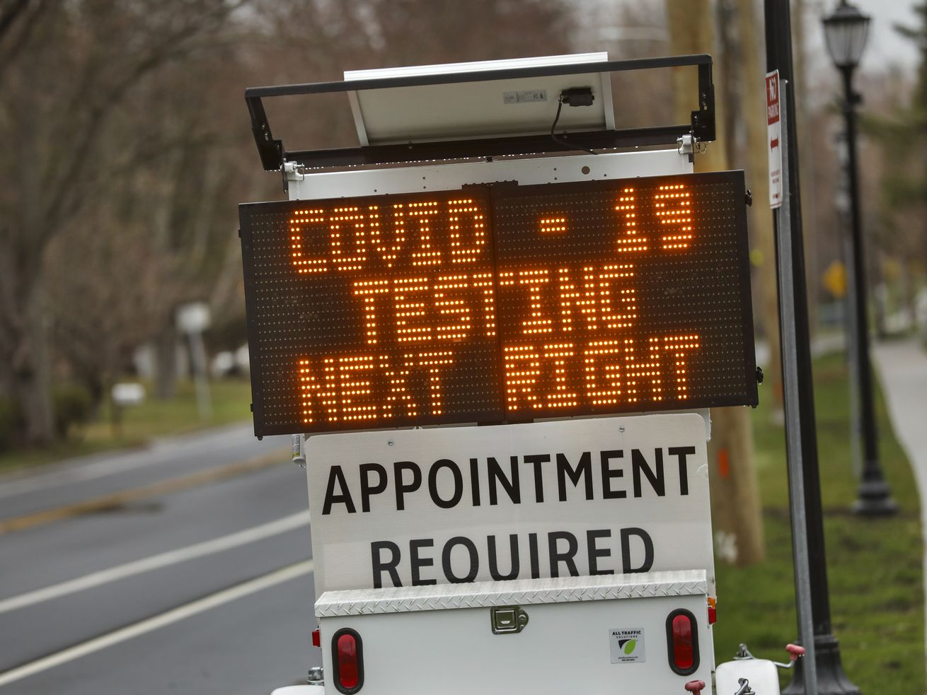 """A digital sign on a street reads, """"Covid-19 testing next right. Appointment required."""""""
