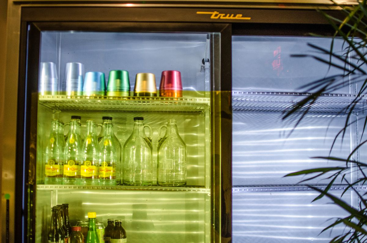 A fridge behind a restaurant is full of colorful aluminum cups, bottles of beer, and more