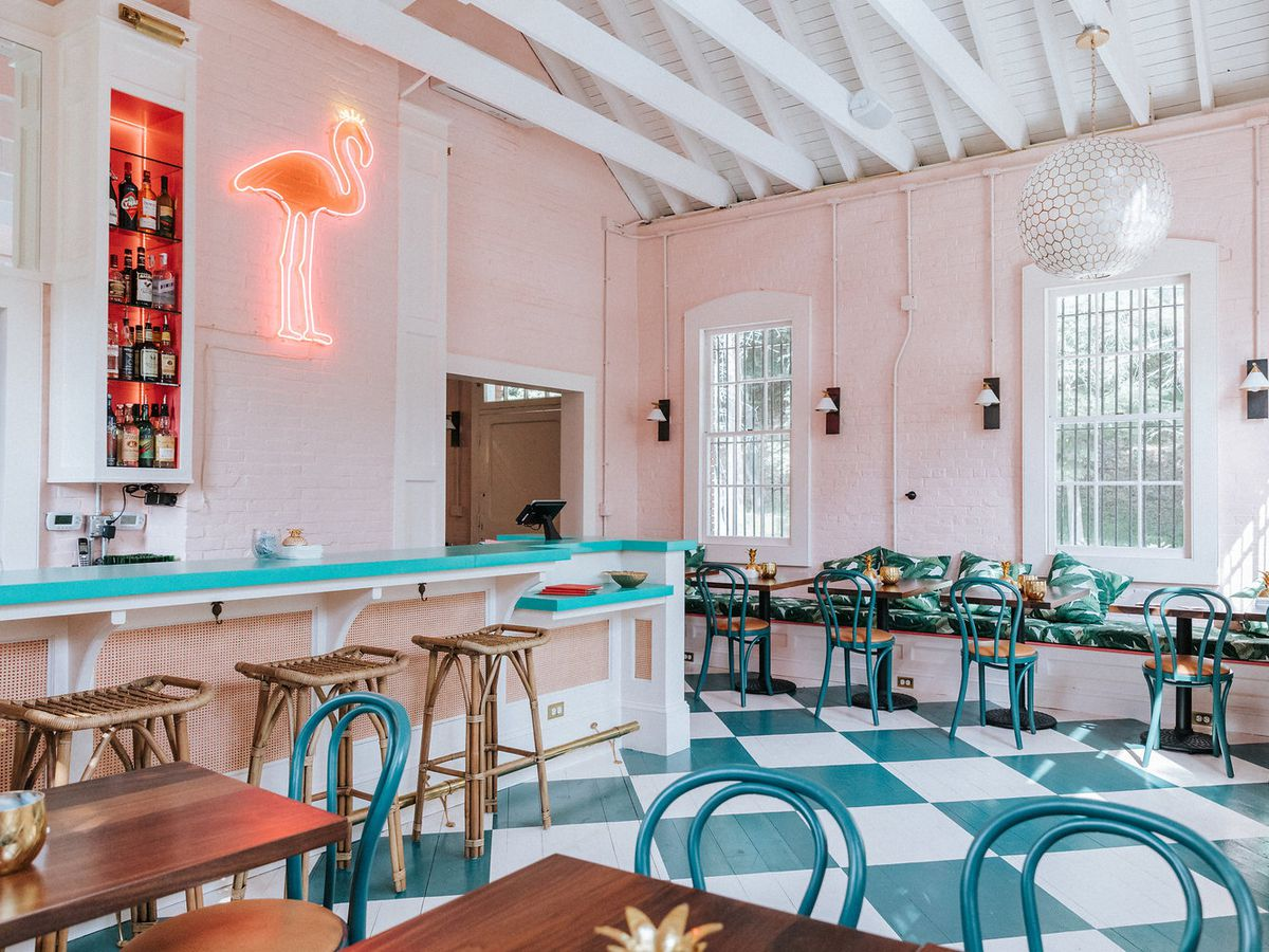 A restaurant interior with checkered floor, wooden tables with bowed wooden backs, a bar with wooden stools, a neon flamingo on the backbar beside bottles and light pouring through windows