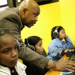 """Roscoe Orman, better known as Gordon on """"Sesame Street,"""" helps children to listen to audiobooks on computers during an event at the Boys and Girls Club in New York, on Wednesday, Oct. 8, 2008."""