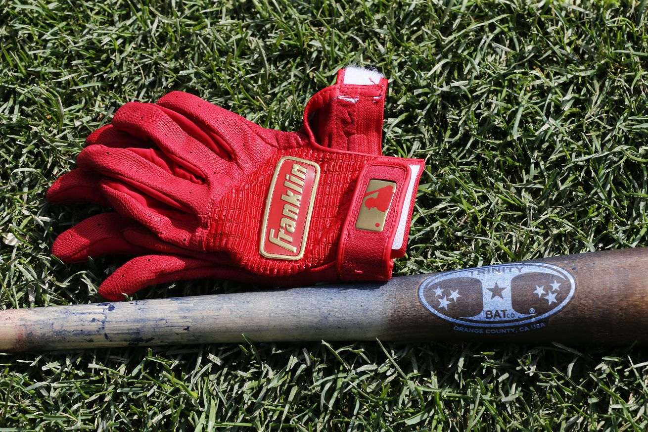 A bat and a set of Franklin baseball gloves belonging to Ben Zobrist #18 of the Chicago Cubs were sitting on the field non the first day of his return to the club following an absence of several months prior to a game between the Chicago Cubs and the Milwaukee Brewers at Wrigley Field on September 01, 2019.
