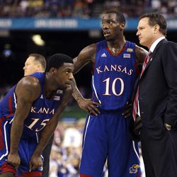 Kansas head coach Bill Self talks to guard Elijah Johnson (15) and guard Tyshawn Taylor (10) during the second half of the NCAA Final Four tournament college basketball championship game Monday, April 2, 2012, in New Orleans.