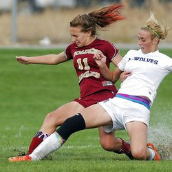 Breanna Brown of Timpanogos and Maple Mountain's Sophie Card (11) battle for the ball on a wet field Tuesday.