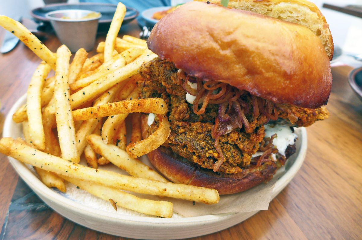 A piled high fried chicken sandwich on a brown bun with fried onions on top and french fries on the side.