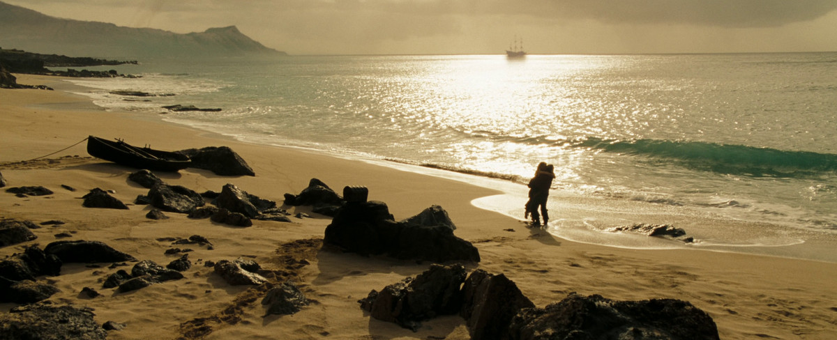 Elizabeth (Keira Knightley) and Will (Orlando Bloom) embrace on a beach