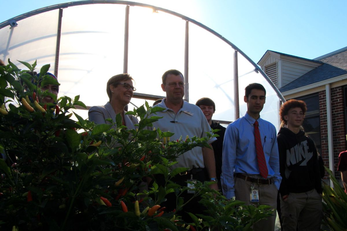 Katie Wilson of the U.S. Department of Agriculture admires Kingsbury High School's edible garden while touring the Memphis school with teachers and students.