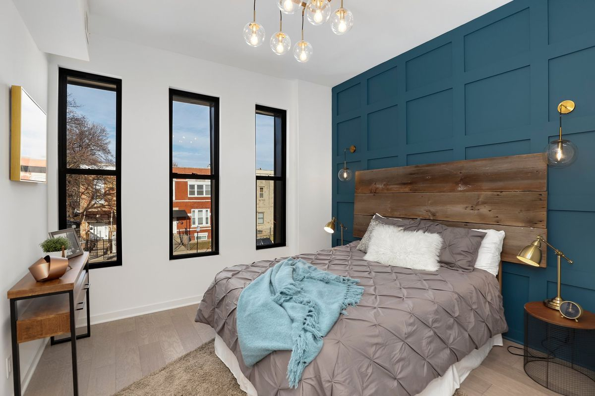 The main bedroom with a teal accent wall, a bed with a wooden headboard, and two side tables.