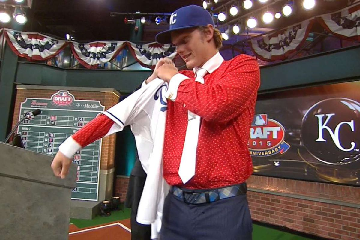 Ashe Russell, 21st overall pick in the 2015 MLB Draft, puts on a Kansas City Royals jersey with assistance by MLB Commissioner Rob Manfred
