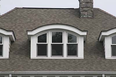 White eyebrow shaped dormer on top of curvy brown roof.