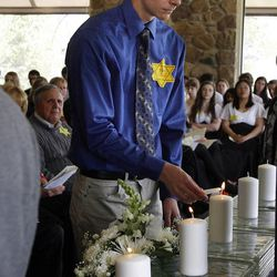 Corey Wolf, vice president of Hillel for Utah at Westminster College, lights a memorial candle during a Utah Holocaust Memorial Commemoration at the Jewish Community Center in Salt Lake City, Thursday, April 19, 2012.