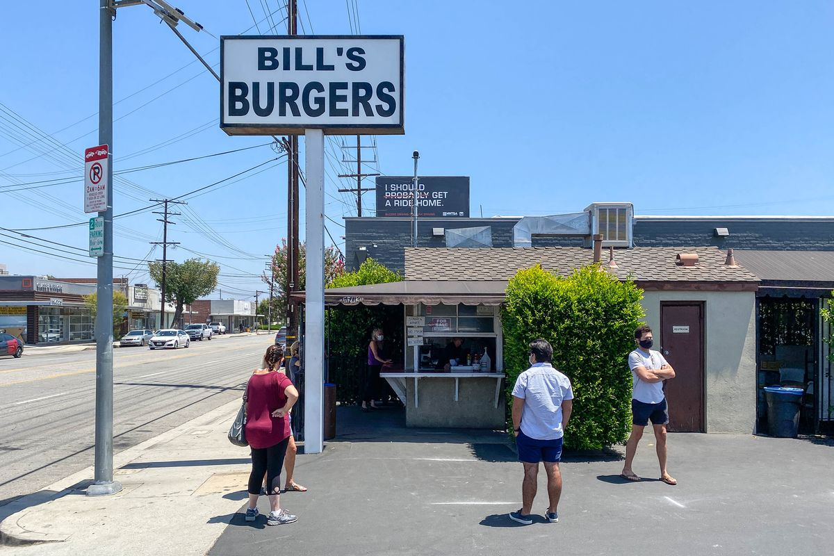 Fans mingle in masks outside of a standalone burger building in a parking lot, under the sun.