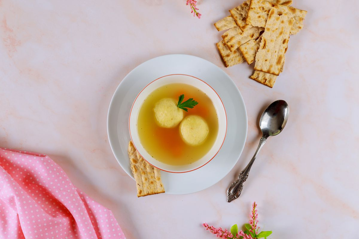 Overhead view of a bowl of matzo ball soup, a spoon, and several pieces of matzo on a pale pink tablecloth