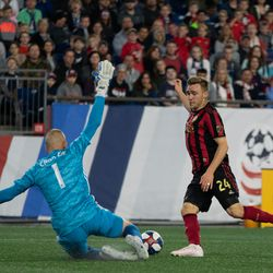 FOXBOROUGH, MA - APRIL 13: Atlanta United FC midfielder Julian Gressel #24 avoids the New England Revolution goalkeeper Cody Cropper #1 during the first half goal at Gillette Stadium on April 13, 2019 in Foxborough, Massachusetts. (Photo by J. Alexander Dolan - The Bent Musket)