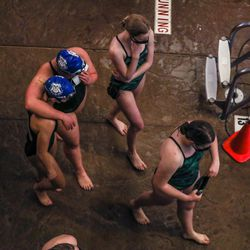 Swimmers walk past after their races at the 3A women's swimming state meet at the South Davis Recreation Center in Bountiful on Saturday, Feb. 13, 2021.