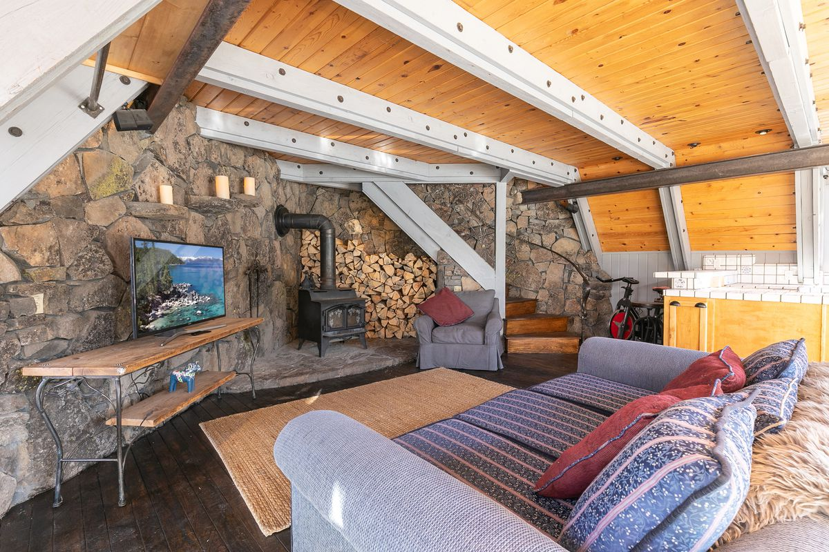 A living room with exposed granite, wood-burning stove, and blue couch.