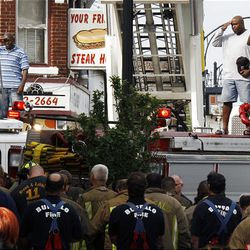 Buffalo firefighters salute as they remove bodies of fellow firefighters from a building after a fire in Buffalo, N.Y., Monday.