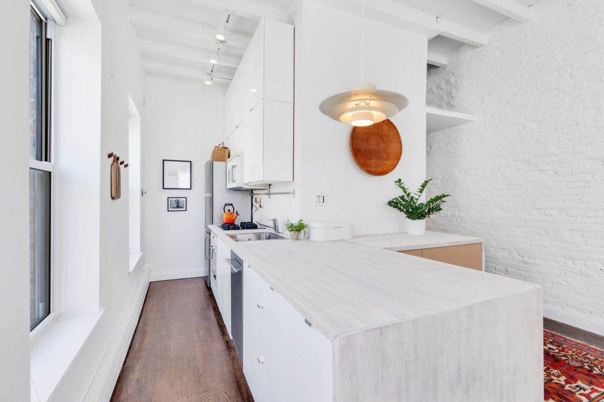 A kitchen with white cabinetry and an island next to it.