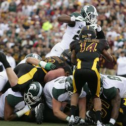 Michigan State's Le'Veon Bell, top, goes over the pile to score a first-quarter touchdown against Central Michigan during an NCAA college football game on Saturday, Sept. 8, 2012, in Mount Pleasant, Mich.