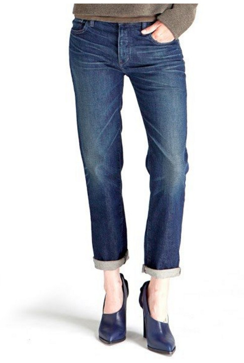Model wearing relaxed-fit jeans cropped and rolled at the ankle with navy blue heels