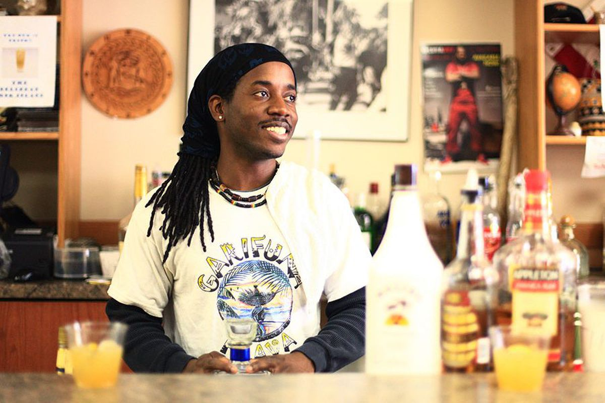 A man with dreads sits at a table, smiling.