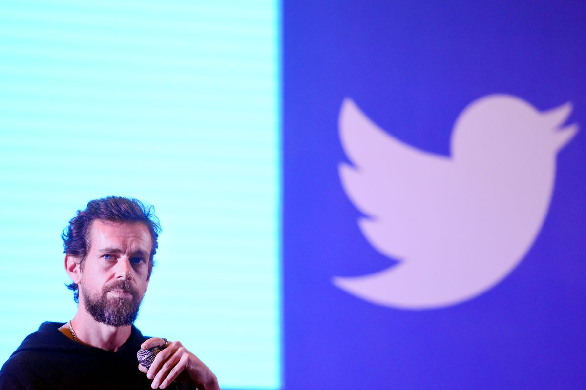Twitter CEO Jack Dorsey holding a microphone onstage and standing in front of the Twitter bird logo.