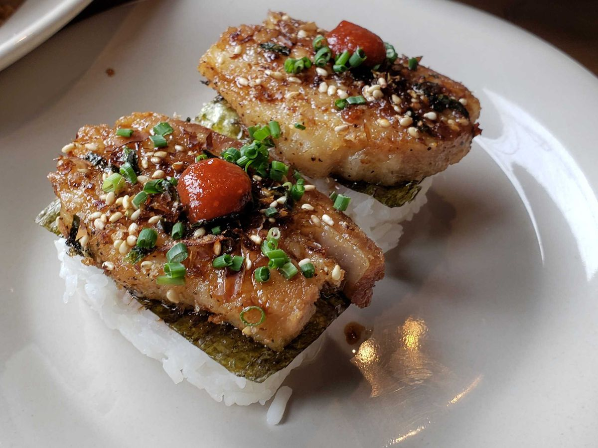 Two pieces of pork belly sushi.