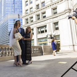Perla and Edgar Bernal and a family member take a photo near the Wrigley Building on N Michigan Ave during the Meet Me on The Mile Sunday Spectacle Sunday, Sept. 26, 2021. 50 couples were | Anthony Vazquez/Sun-Times
