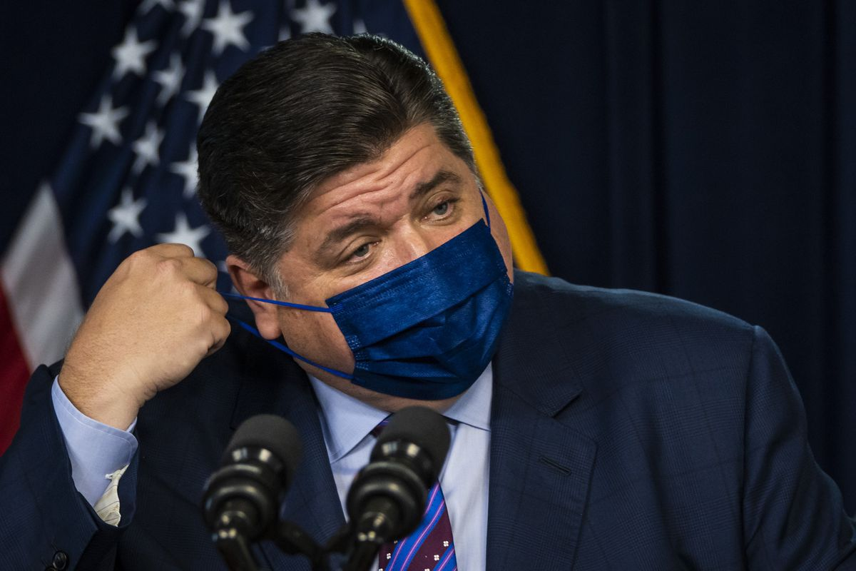 """Gov. J.B. Pritzker adjusts his face mask as he speaks during an Aug. 26 news conference in the Loop. Pritzker said he's """"hopeful"""" Illinois is nearing a peak of the Delta variant resurgence."""