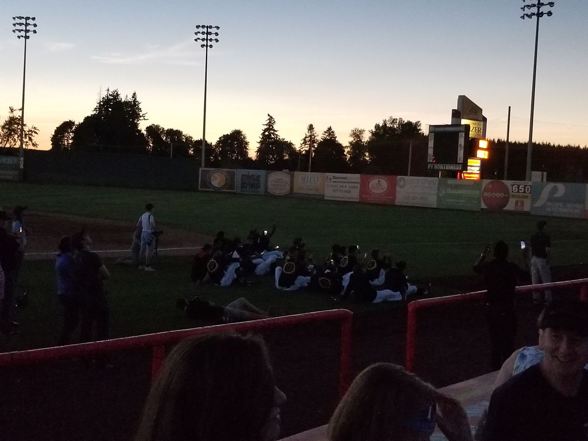 Volcanoes players watch the eclipse and take photos while seated together on the field, now in the dark