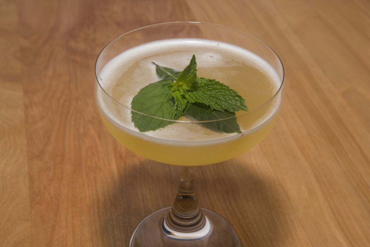 A yellow cocktail with a big green leaf in stemmed glass.