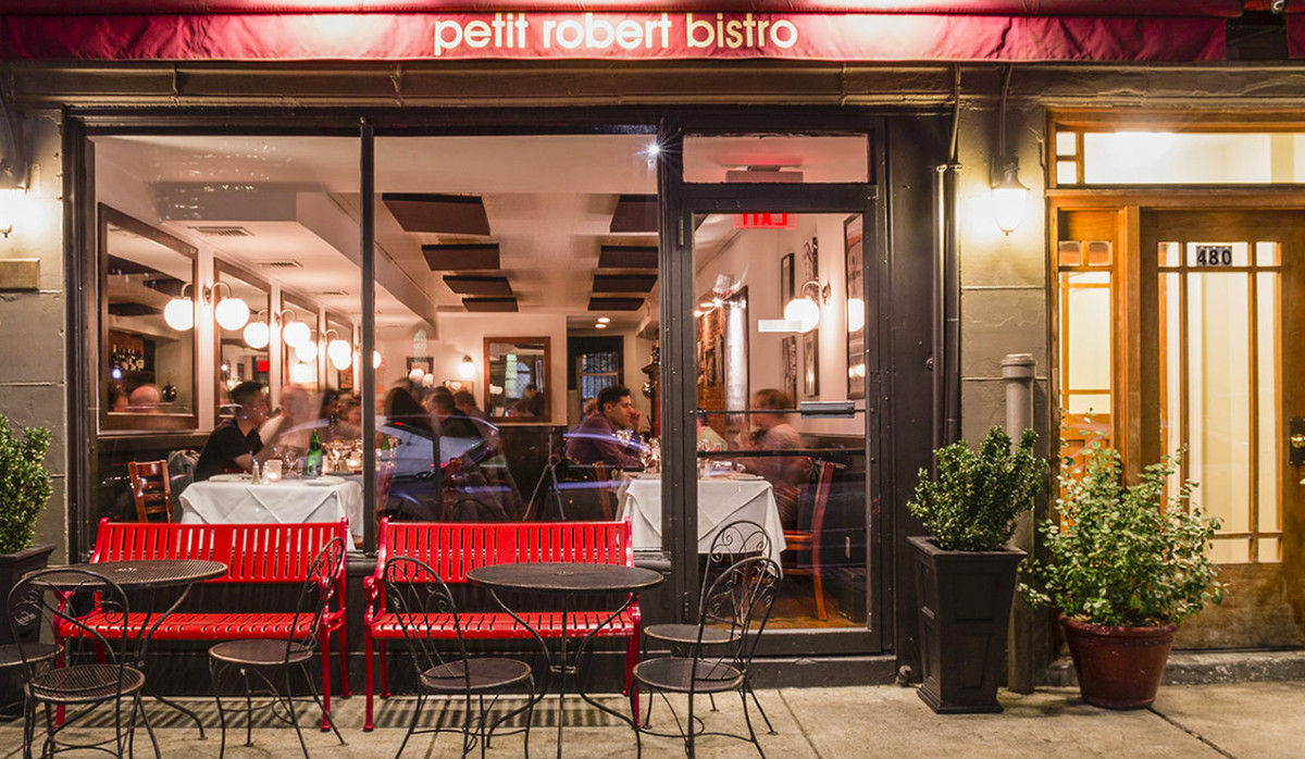 Exterior photo of a restaurant with a floor-to-ceiling window along the front. A red banner at the top has the restaurant's name on it, Petit Robert Bistro.