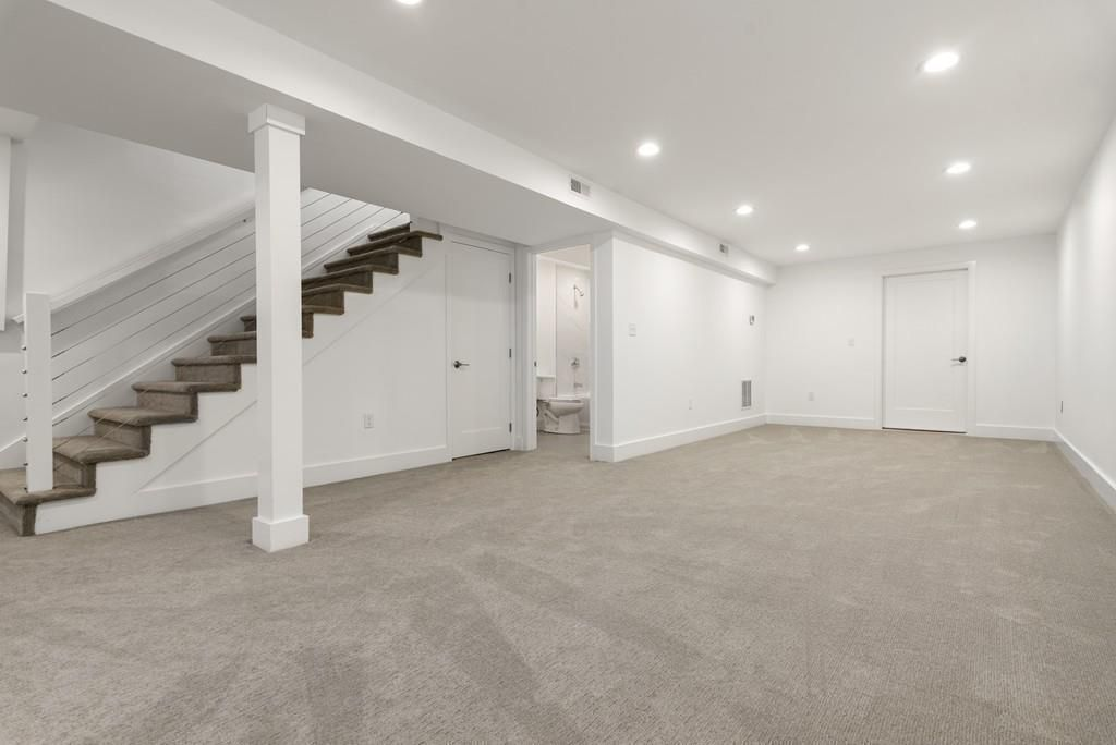 A long, empty downstairs room beside some stairs.