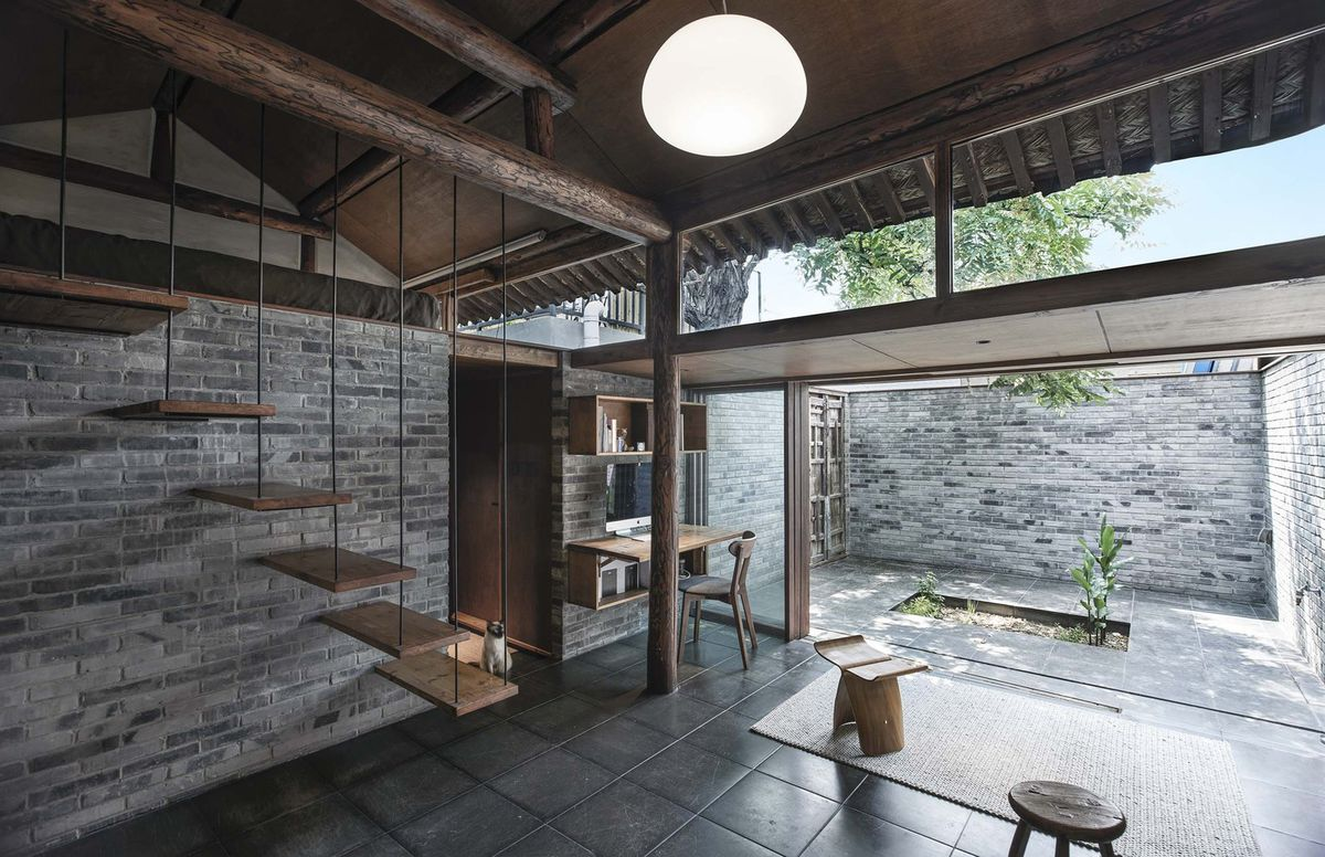 Interior of small home with view out onto a courtyard and floating stair treads.