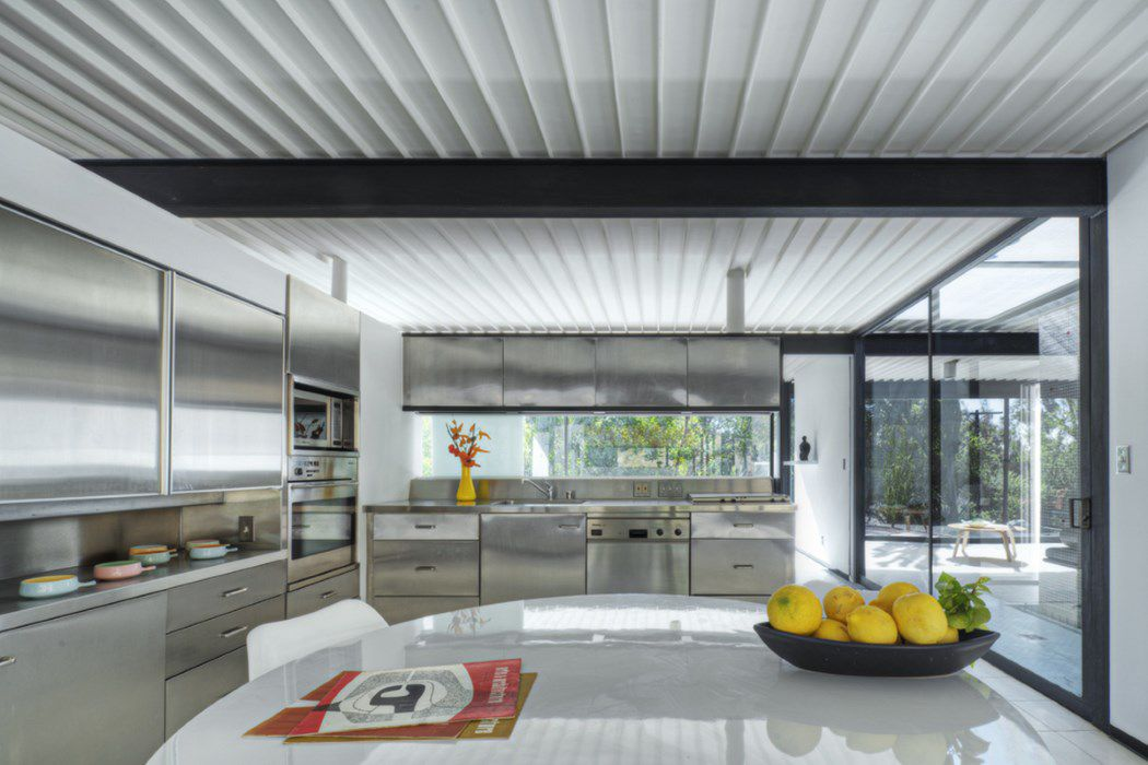 A midcentury modern kitchen with a white wood ceiling and silver cabinetry. There is a table, chairs, and tall windows.