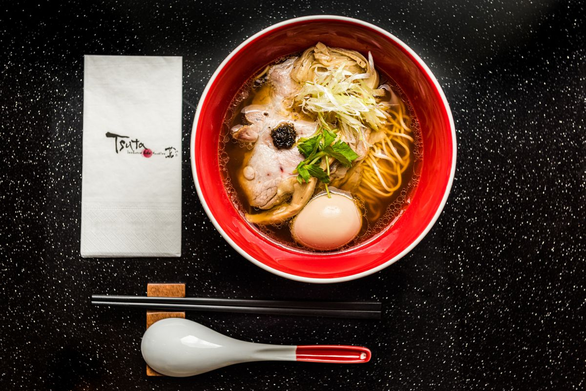 A bowl of ramen with pieces of sliced pork floating at the top