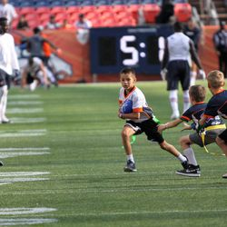A future NFLer? makes a cut looking up field during the NFL's FLAG Football game, prior to the Broncos/Bears preseason game.