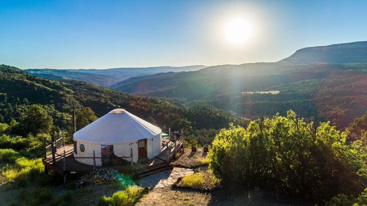 An aerial view of a yurt in Utah. The facade is white. The yurt is situated on a cliff's edge overlooking mountains.