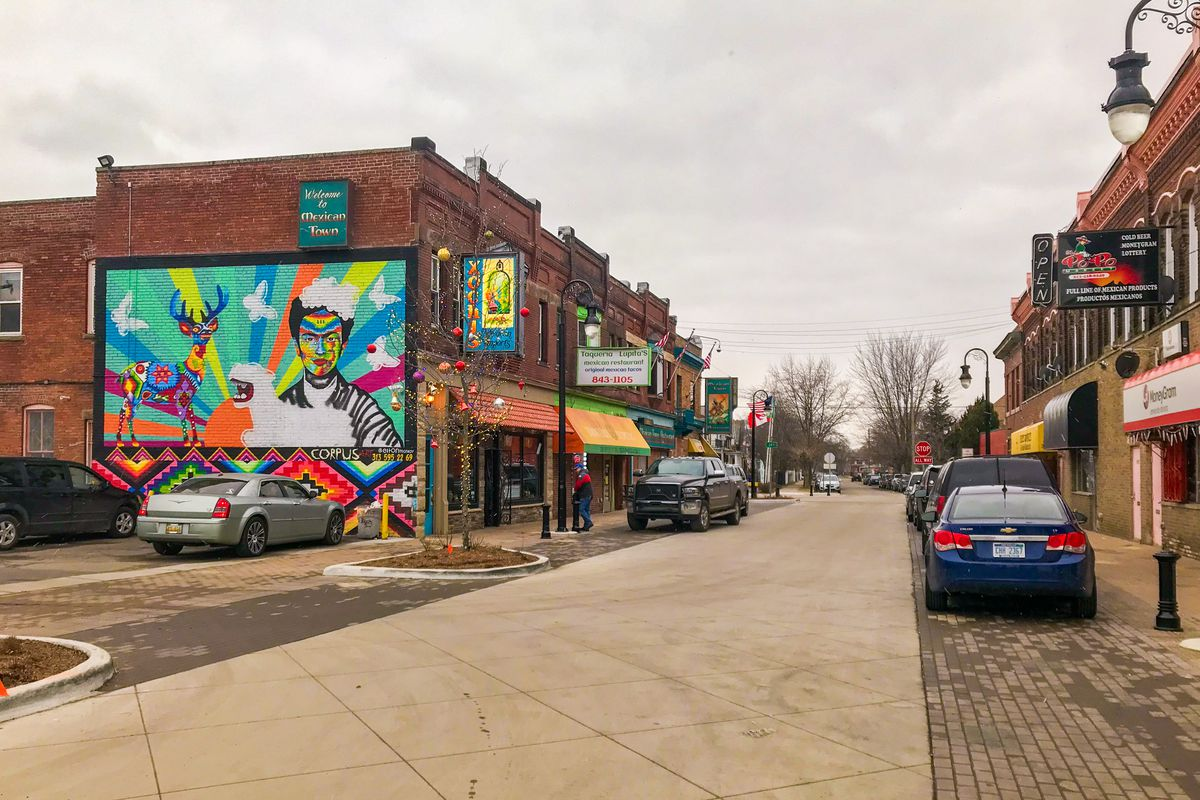 A street made of cement blocks that level with the sidewalk. Several cars are parked on pavers along the street. There's a colorful mural in primary colors of Frieda Kahlo on the side of a building.