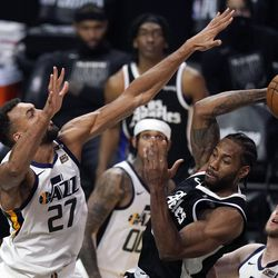 Los Angeles Clippers forward Kawhi Leonard, right, passes the ball as Utah Jazz center Rudy Gobert defends during the second half of Game 3 of a second-round NBA basketball playoff series Saturday, June 12, 2021, in Los Angeles.