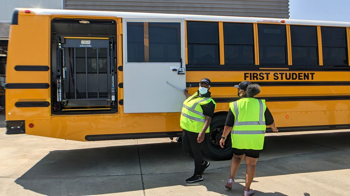 Two employees, wearing yellow reflective vests, open a wheelchair access door on a First Student school bus.