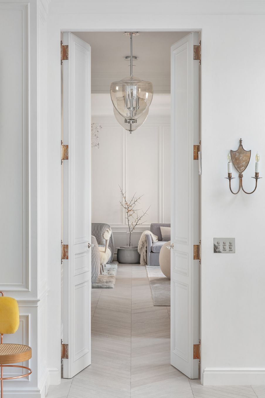 Two tall white doors that open up to a bedroom.