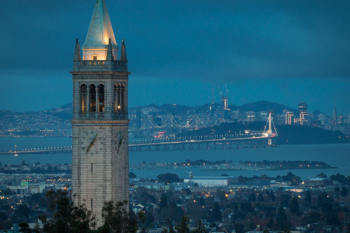 A view of the bay with Berkeley's Sather Tower in the foreground at dusk.