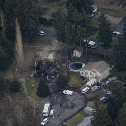 The smoldering remains of a house, left, where an explosion killed Josh Powell and his two sons, Sunday, Feb. 5, 2012, is shown from the air in Graham, Wash. The explosion occurred moments after a Child Protective Services worker brought the two boys to the home for a supervised visit. Powell's wife Susan went reportedly missing from their West Valley City, Utah, home in December 2009.