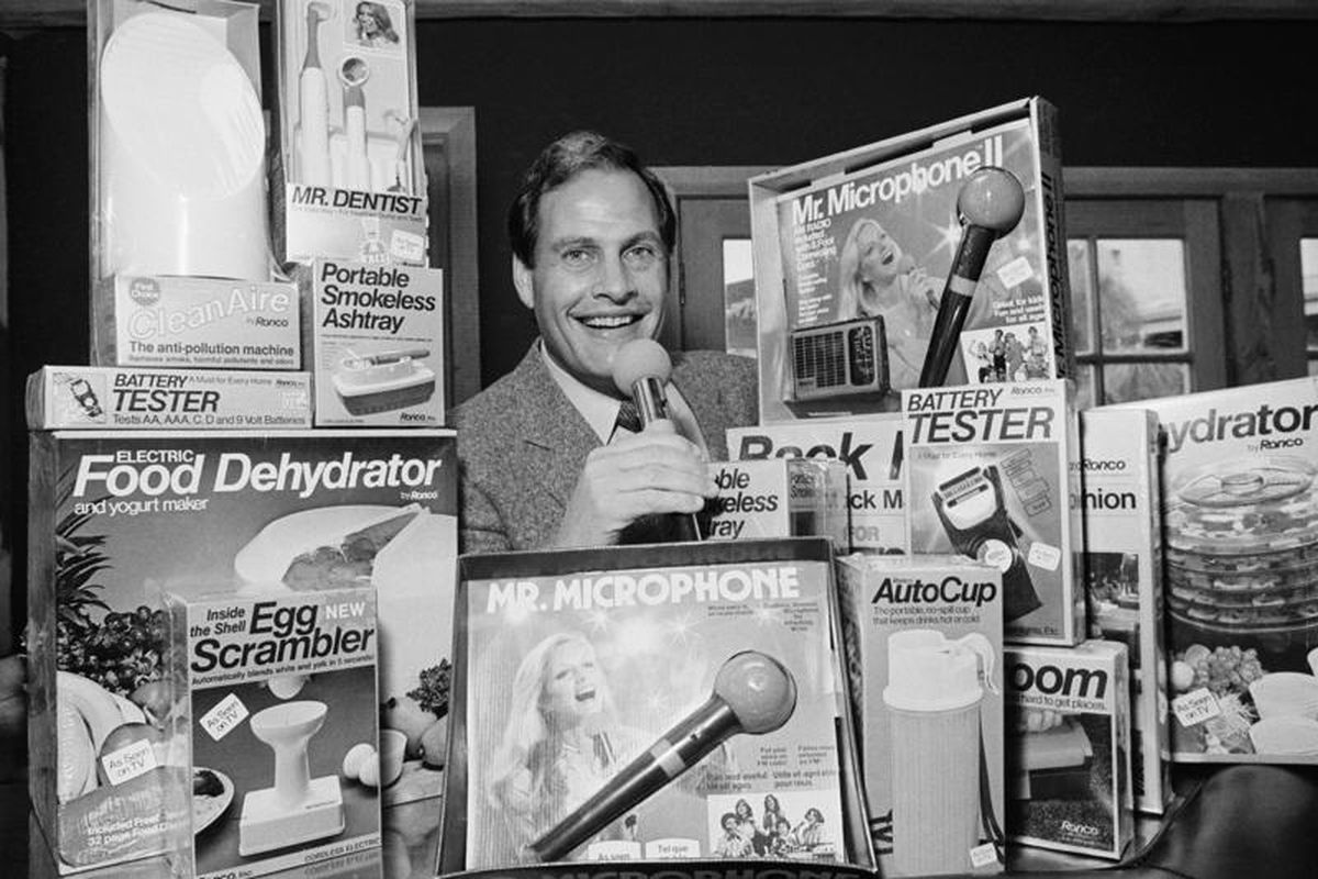 In this Wednesday, Dec. 8, 1982, file photo, Ron Popeil, the man behind those late-night, rapid-fire television commercials that sell everything from the Mr. Microphone to the Pocket Fisherman to the classic Veg-a-Matic, sits surrounded by his wares in his office in Beverly Hills, California. Ron Popeil died Wednesday, July 28, 2021 his family said.