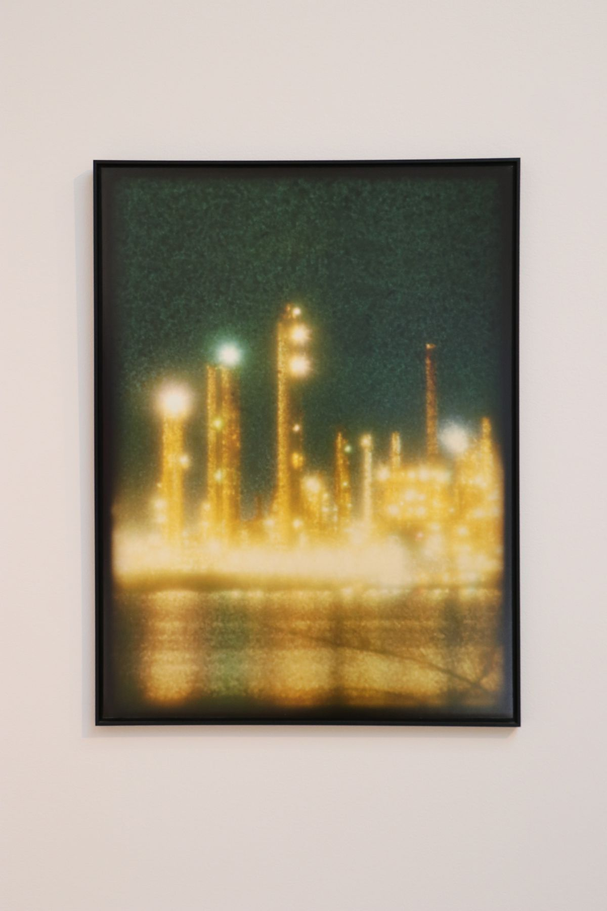 A blurry photography of an illuminated oil refinery hangs on a gallery wall