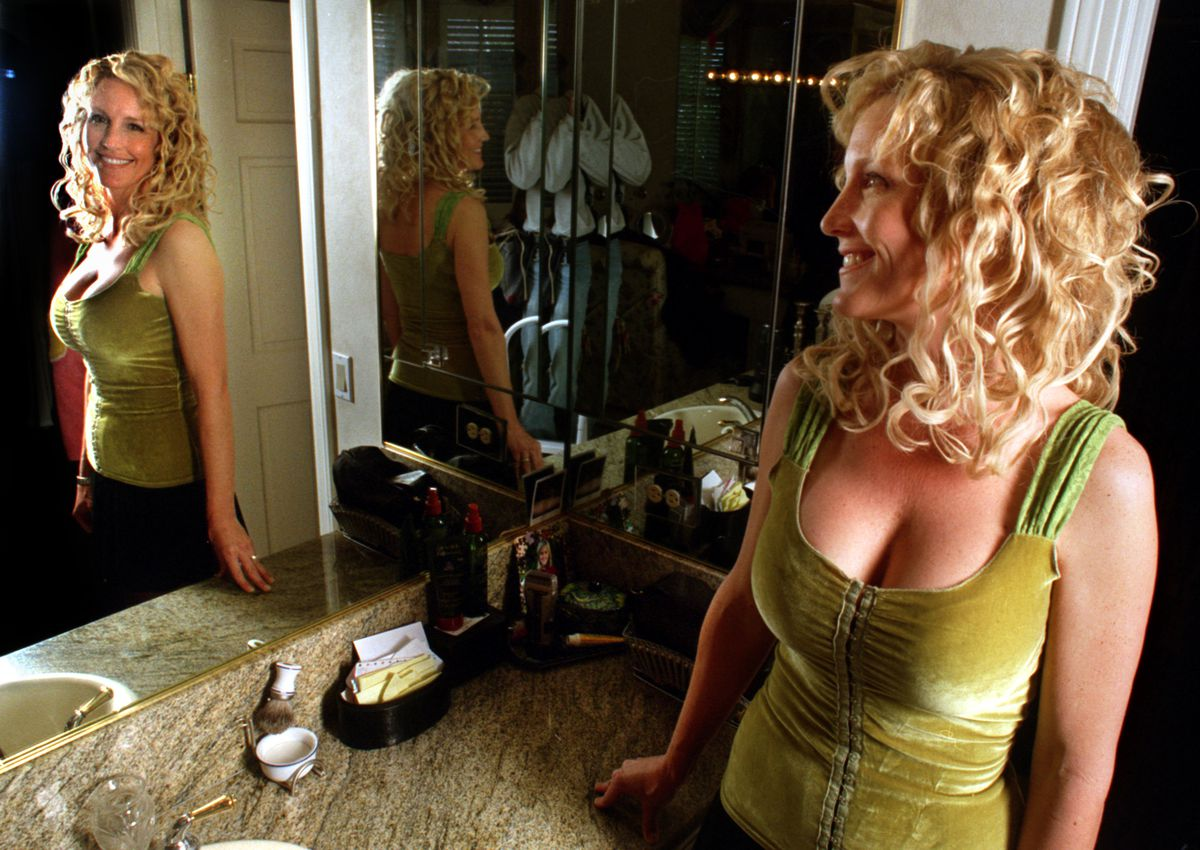 Erin Brockovich, wearing a hook and eye top, her favorite, stands in dressing room area at her home