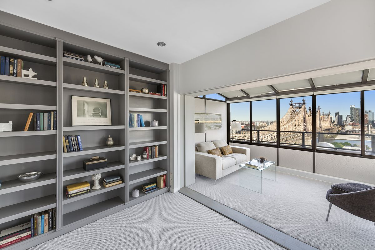 A living area with a large bookshelf, a beige rug, and light grey walls.