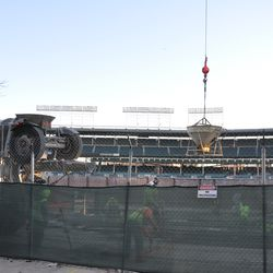 Concrete filled bucket being lifted next to the bleacher wall on Waveland