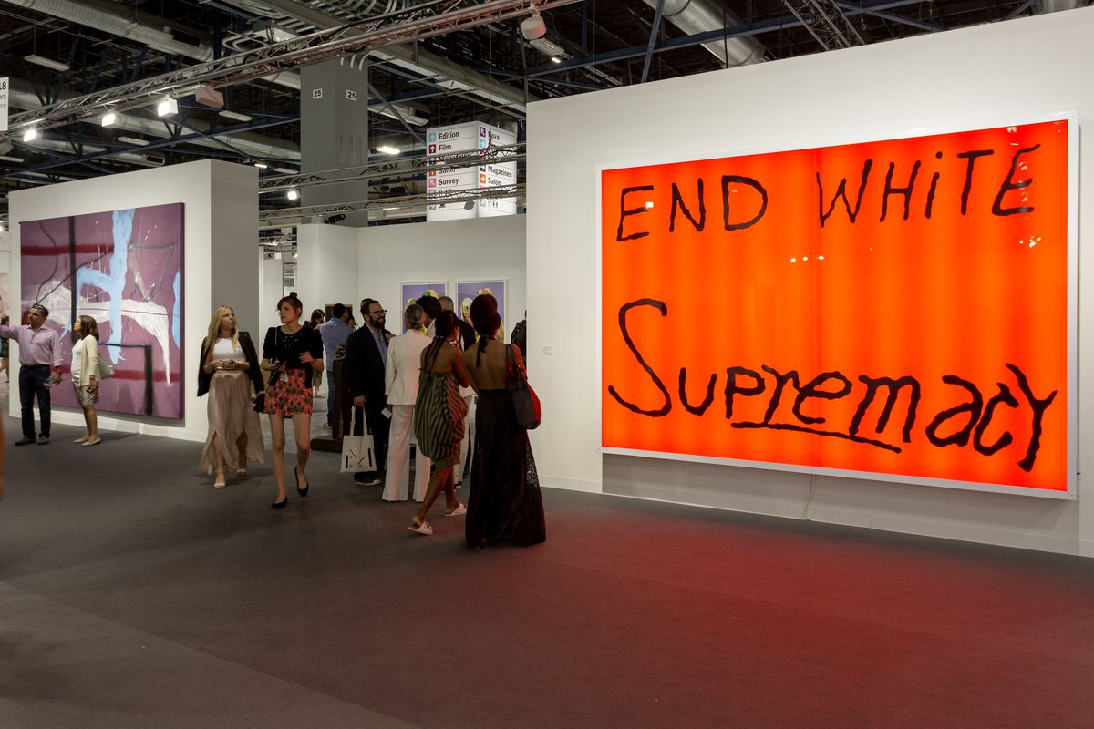 Large orange canvas with END WHITE Supremacy written on it in black paint, on a wall at the Art Basel Miami art fair.