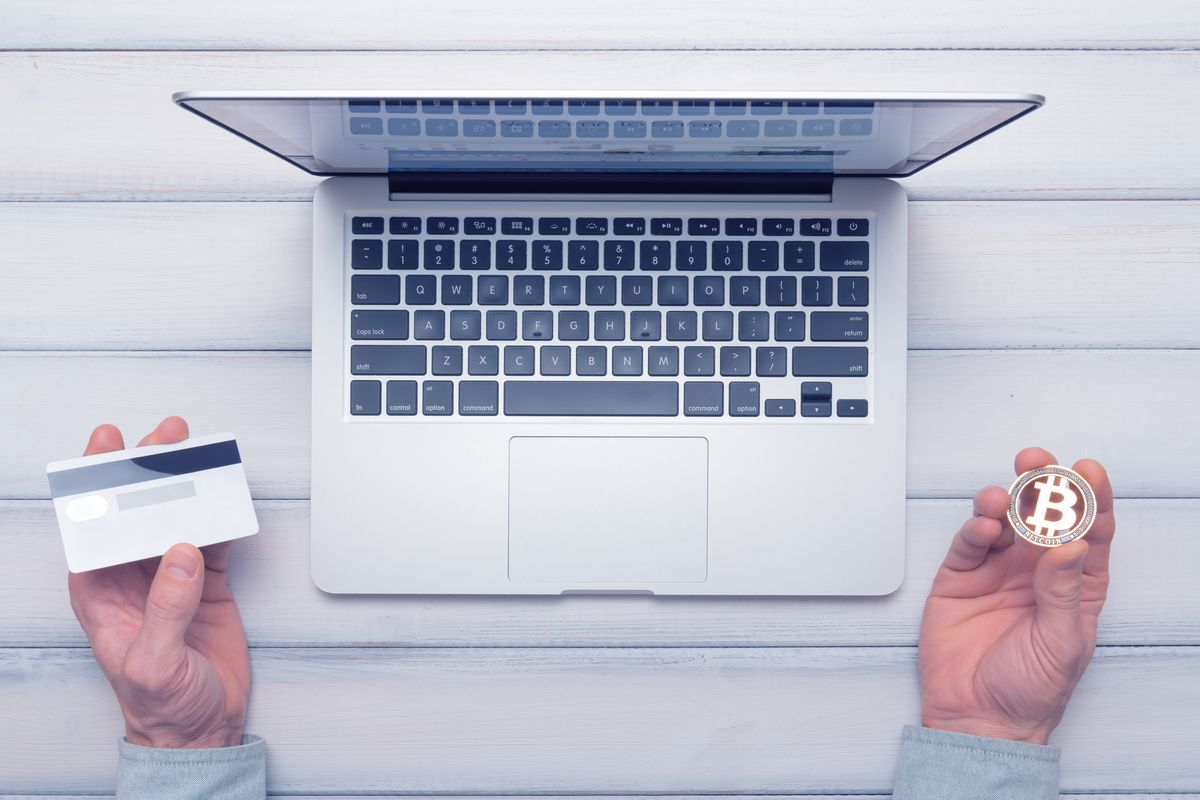 A laptop open on a table with a hand holding a credit card on one side and a hand holding a bitcoin representation in the other.